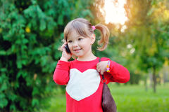 Little girl speaks by phone Stock Images