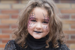 Little girl with spider web painted on face Royalty Free Stock Photography