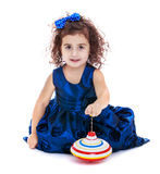Little girl spinning dreidel sitting on the floor Stock Photography