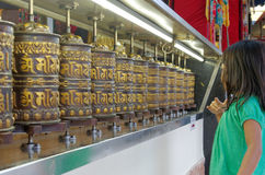 Little girl spinning prayer wheels. In thekchen choling temple, singapore Stock Photos