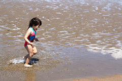 Little girl splashing and playing at the beach Royalty Free Stock Photos