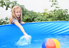 Little girl splashing water Stock Images