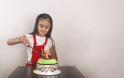 Little girl splitting the birthday cake stock photos