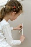 Little girl spoiled the wallpaper. Stock Photo
