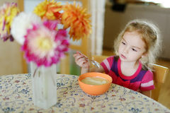 Little girl with a spoon of porridge Stock Images