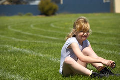 Little girl on sports day tying laces stock photo