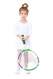 Little girl in sports dress holding a tennis Stock Photos