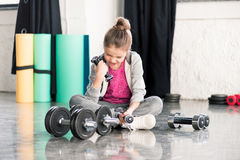 Little girl in sportswear sitting on floor and exercising with dumbbells Royalty Free Stock Photos