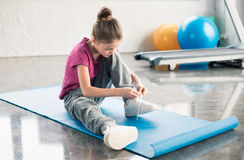 Little girl in sportswear sitting on mat and tying shoelace in gym Royalty Free Stock Images