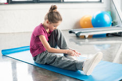 Little girl in sportswear sitting on mat and tying shoelace in gym Royalty Free Stock Image
