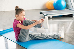 Little girl in sportswear sitting on yoga mat and tying shoelace Stock Photos