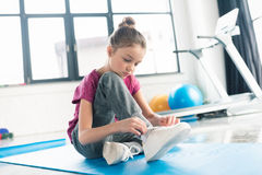 Little girl in sportswear sitting on yoga mat and tying shoelace Royalty Free Stock Photos