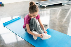Little girl in sportswear sitting on yoga mat and tying shoelace Royalty Free Stock Photography