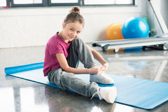 Little girl in sportswear tying shoelace and smiling at camera Stock Photography