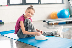 Little girl in sportswear tying shoelace and smiling at camera Stock Image
