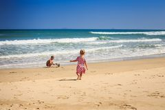 Little Girl in Spotty Runs to Wave Surf Boy Plays on Beach. Backside view little blond girl with pig-tails in spotty pink dress runs to wave surf boy squats Royalty Free Stock Photo