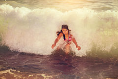 Little girl in the spray of waves at sea Stock Photography
