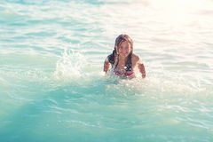 Little girl in the spray of waves at sea Stock Photo