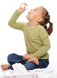 Little girl spraying her nose stock images