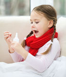 Little girl spraying her nose Royalty Free Stock Photography