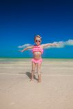 Little girl spread her arms standing at the white Royalty Free Stock Image