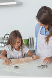 Little girl spreading a dough with a rolling spin Royalty Free Stock Images