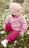 Little girl in spring. Little girl sitting in a forest full of spring flowers Royalty Free Stock Image