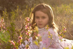 Little girl with spring flowers in nature Royalty Free Stock Photos