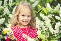 Little girl in spring flowers Stock Images