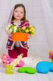 Little girl with spring flowers in  vase Stock Images