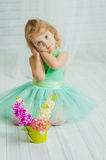 Little girl with spring flowers in  vase Stock Photos