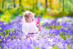 Little girl in a spring forest. Adorable little girl with curly hair wearing a white dress playing with a wind toy on a walk in spring forest with blue bell royalty free stock photo