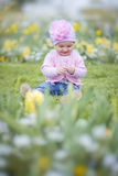 Little girl in spring park. Happy little girl playing with flowers Stock Photo