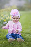 Little girl in spring park. Happy little girl playing with flowers Royalty Free Stock Image