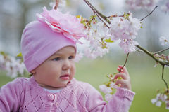 Little girl in spring park. Happy little girl playing with flowers Royalty Free Stock Photo