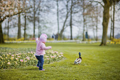 Little girl in spring park. Happy little girl playing with flowers Royalty Free Stock Photos