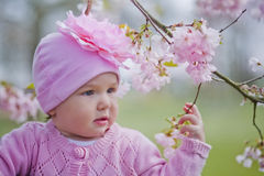 Little girl in spring park. Happy little girl playing with flowers of sakura Stock Photo