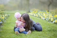 Little girl in spring park. Happy little girl playing with mother Stock Photo