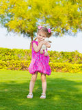 Little girl in spring park. Photo of cute little girl holding in hands soft toy, sweet baby playing outdoors, adorable small female having fun on backyard in Stock Photo