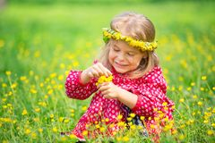 Little girl in spring park. Portrait of happy little girl on a flower field Royalty Free Stock Photo