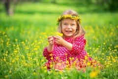 Little girl in spring park. Portrait of happy little girl on a flower field Royalty Free Stock Image