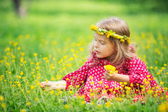 Little girl in spring park. Portrait of happy little girl on a flower field Stock Photo