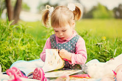 The little girl in spring park reads the book in Stock Image