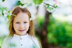 Little girl spring portrait. Adorable little girl in in blooming apple tree garden on spring day stock photos