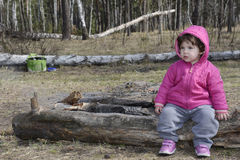 Little girl in spring sitting in the woods on a log. Stock Photo