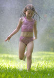 Little Girl in Sprinkler Stock Images