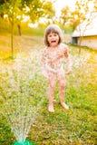 Little girl at the sprinkler having fun, summer garden Stock Images