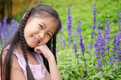 Little girl squat in flowers Royalty Free Stock Photos