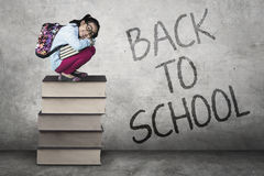Little girl squat on textbooks Royalty Free Stock Photography