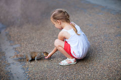 Little girl and squirrel Royalty Free Stock Images